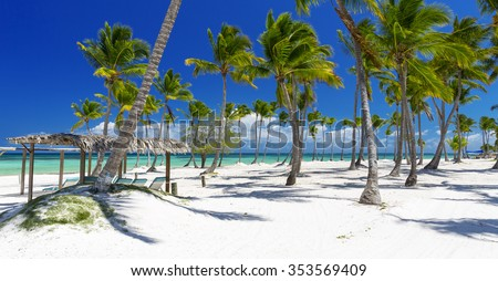 Beach on the tropical island. Clear blue water, sand and palm trees. Beautiful vacation spot, treatment and aquatics. Rest, relaxation, SPA, solar bathtubs, sea salt. - stock photo