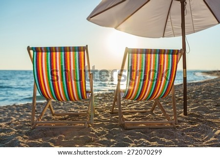Beach. Pair of beach loungers on the deserted coast sea at sunrise. - stock photo