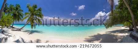 Beach panorama at Maldives with blue sky, palm trees and turquoise water - stock photo