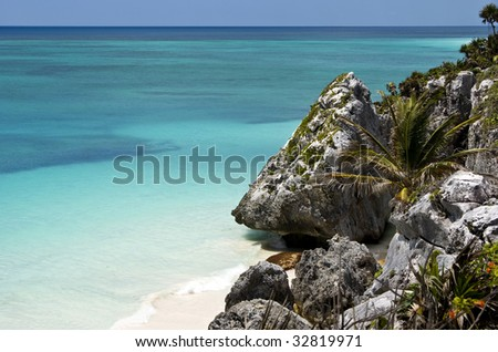 Beach paradise, rocky cliff and turquoise sea in Tulum Mexico. - stock photo