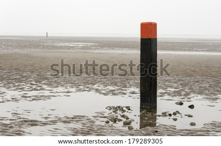 beach pole on wet sand and mud at low waterlevel