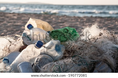 Beach pollution. Plastic bottles and other trash on sea beach - stock photo