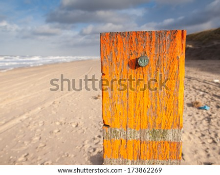beach post with orange flaking paint carrying a metal marker nail indicating the dutch standard sea level datum point the Amsterdam Ordnance Datum (Normaal Amsterdamse Peil or NAP). - stock photo