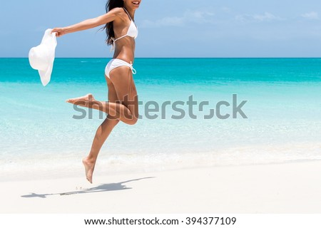 Beach ready bikini body - sexy slim legs and toned thighs and butt. Suntan happy woman jumping in freedom on white sand with sun hat. Weight loss success or epilation concept. - stock photo