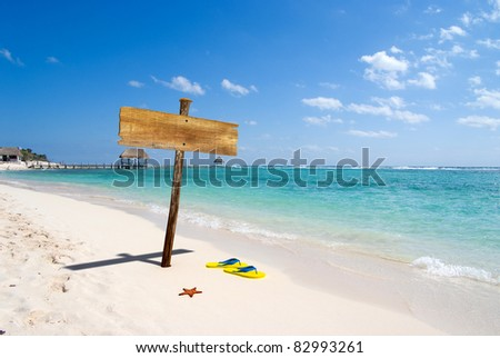 Beach resort and a blank wooden signpost - stock photo