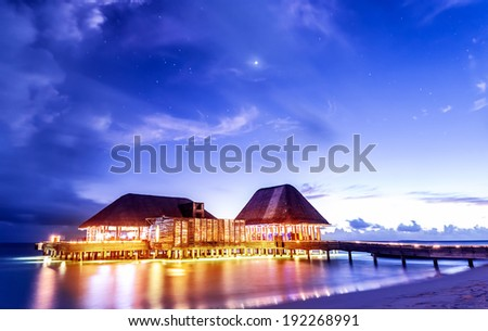 Beach restaurant glowing with bright lights in the night, romantic place for date on tropical island, summer holidays concept - stock photo