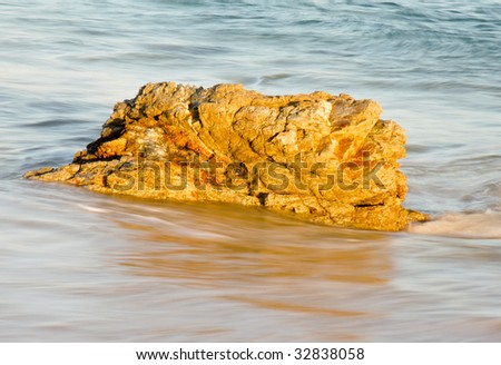 Beach rock washed over by waves - stock photo