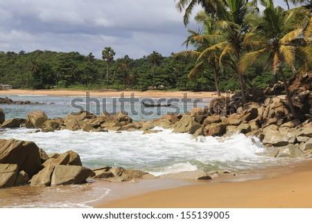 Beach, rocks, palm trees and boat in Axim, Ghana - stock photo