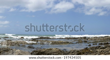 beach rocky tide pool with ocean waves and beautiful blue cloudy sky background - stock photo