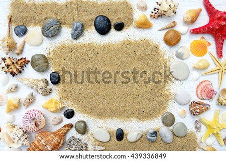 Beach sand, pebbles, sea shells and starfish on a white wooden background - stock photo