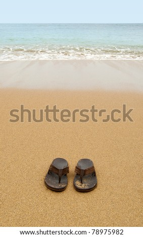 Beach sandals or tongs on a sandy beach with lots of background copyspace - stock photo