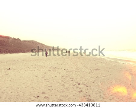 Beach scene in the evening with people walking along the coastline. winter scene at the beach of Sylt. - stock photo
