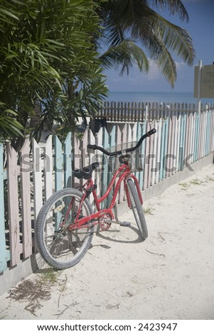 Beach scene of a bicycle near a picket fence - stock photo