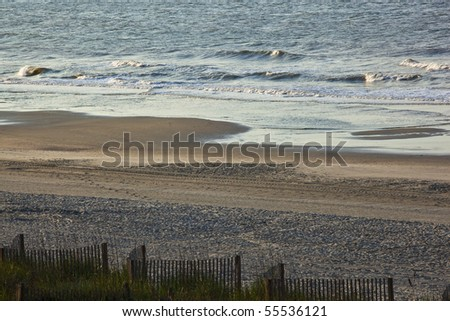 Beach scene of sand,surf,dune,sea grass,fence as early morning welcomes a beautiful day at the beach. - stock photo