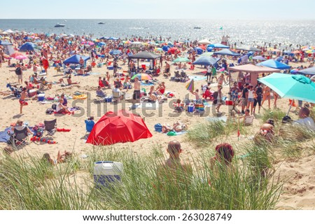 Beach scene on a busy summer day with blurred out people. Focus on grass in foreground  - stock photo