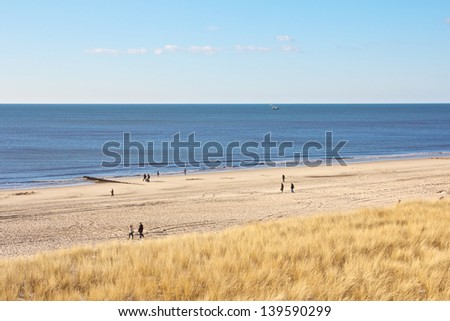Beach scene on Sylt island, Germany, with hikers walking along the shoreline and beach grass on a dune in the foreground - stock photo