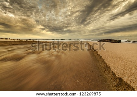 Beach scene showing river mouth in the sand - stock photo