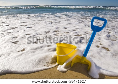 Beach scene, Spade and bucket at the waters edge. - stock photo