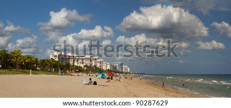 Beach scene with an airship and lighthouse in the background - stock photo