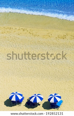 Beach scene with beautiful turquoise sea and yellow sand and sun umbrellas - stock photo