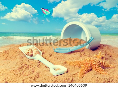 Beach scene with bucket and spade against ocean background with kite flying - stock photo