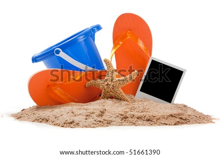 Beach scene with sand, orange flipflops, blue pail, starfish and instant photograph - stock photo