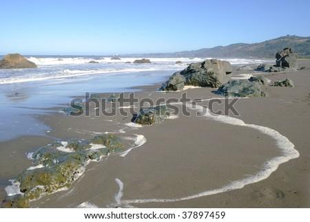 Beach scene with waves, rocks, and sea foam - stock photo
