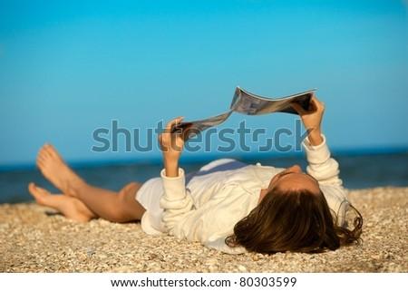 Beach scene. Young woman reading magazine - stock photo