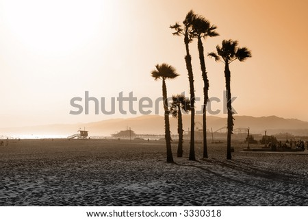 Beach scenery with pier and mountains in background - stock photo