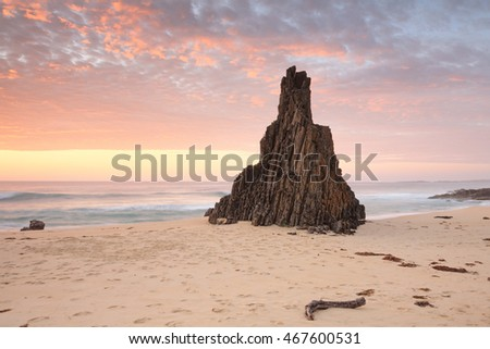 Beach seascape from Meringo, Eurobodalla National park, with magnificent shaped sea stack pointing to an awesome sunrise sky