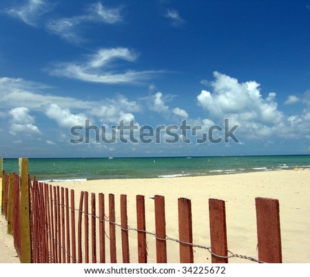 beach seascape with sand fence - stock photo