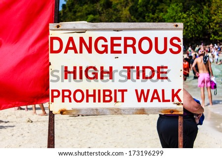 Beach sign that says, Dangerous High Tide Prohibit Walk. - stock photo