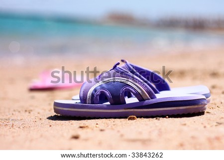 Beach slippers on a sandy beach - stock photo