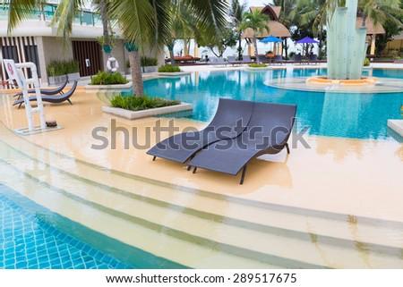 Beach sofa beside swimming pool - stock photo