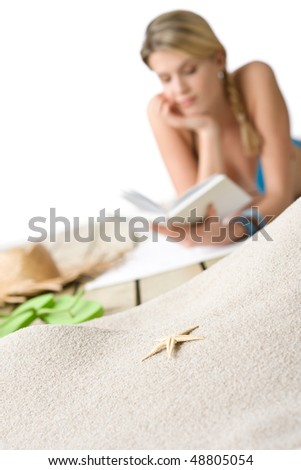 Beach - Starfish on sand, woman with book in background - stock photo