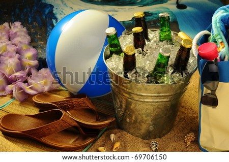 Beach still life with warm afternoon sunlight. Beachball, tote, lotion, sandals, sunglasses and lei surround a bucket of assorted beer bottles on ice. - stock photo