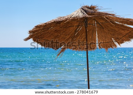 Beach straw umbrella against the bright blue sky and a calm sea. Selective focus on the parasol. - stock photo