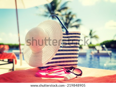beach, summer and vacation and concept - close up of hat, bag, sunscreen and sunglasses at pool - stock photo