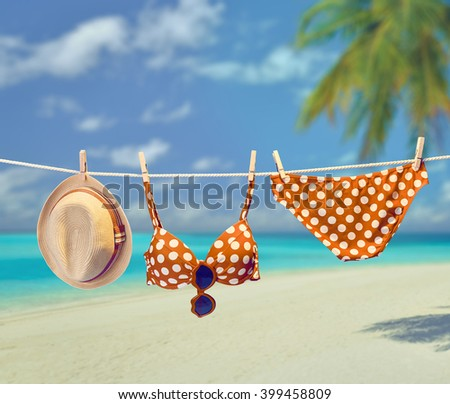 Beach Summer clothes and accessories stylish set. Fashion swimsuit bikini red polka dots, sunglasses hat. Essentials creative look on tropical sea sky background.Hawaii, ocean vacation.Vintage - stock photo