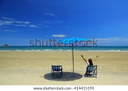 Beach summer girl on island vacation holiday relax in the sun on their deck chairs under a beach umbrella with beautiful blue sky and white cloud - stock photo