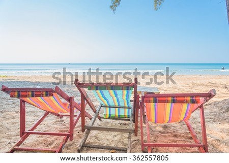Beach summer on island vacation holiday relax in the sun on their deck chairs under a giant tree. Idyllic travel background. Vacation Sunset Concept
