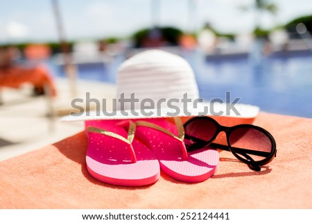 beach, summer, vacation and accessories concept - close up of hat, flip-flops and sunglasses at pool - stock photo
