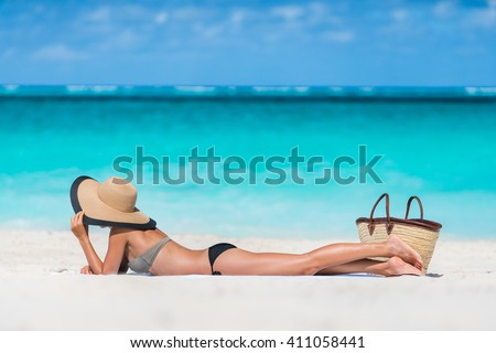 Beach summer vacation woman relaxing sunbathing on white Caribbean sand and turquoise ocean. Young tourist girl lying down on towel by sea wearing bikini and sun hat enjoying summer travel holidays.  - stock photo