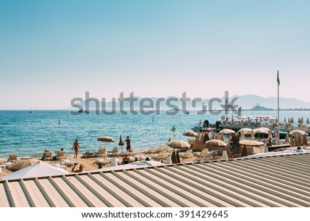 Beach sun loungers. Chaise-longues on the beach. Sunbed and umbrella on beach in Cannes, France. - stock photo