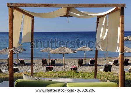 Beach sunbeds and umbrellas on the luxury hotel beach - stock photo