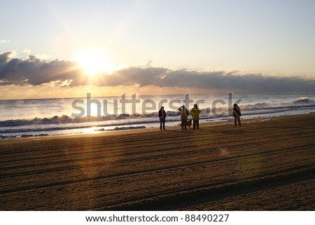 Beach Sunrise with family and dog walking down the beach - stock photo