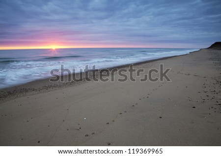 Beach Sunrise with waves crashing on shoreline. - stock photo