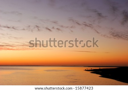 Beach sunset scene with fisherman along the tropical coast of Mozambique, southern Africa - stock photo