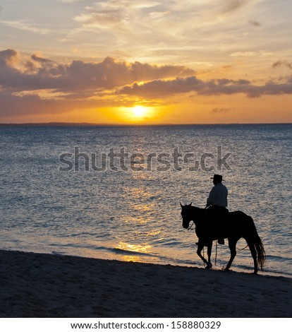 Beach sunset with cowboy - stock photo