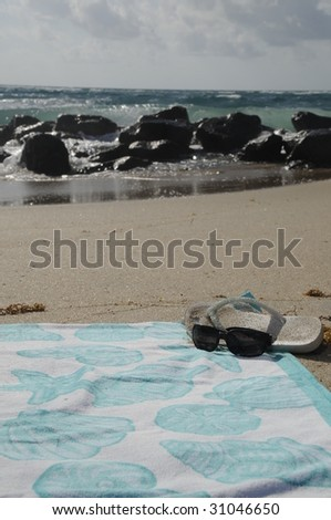 Beach towel and sunglasses in sand at the ocean